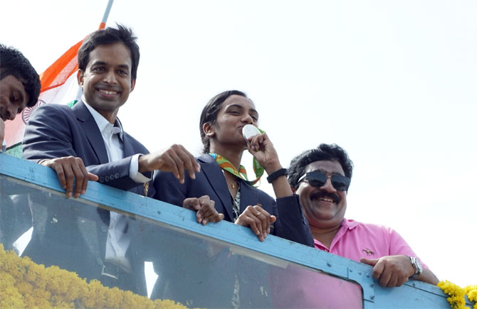 Rio Olympics silver medallist PV Sindhu and coach P Gopichand get a rousing reception atop an open-air bus in Hyderabad on her return from the Rio Games on August 22