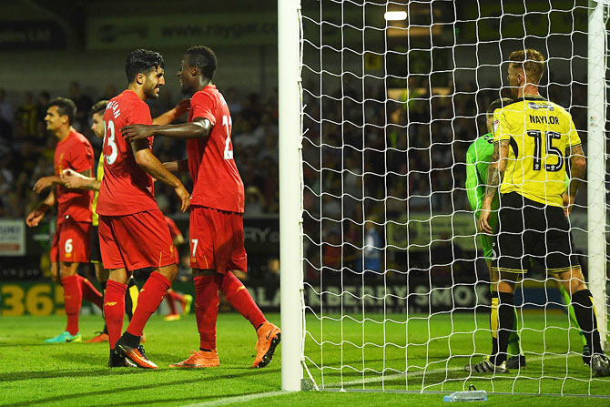 Liverpool's Emre Can (left) and Divock Origi celebrate the own goal scored by Burton Albion's Tom Naylor during their League Cup second round match at Pirelli Stadium in Burton upon Trent, England, on Tuesday