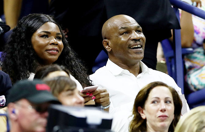Former boxing heavyweight champion Mike Tyson (right) watches the first round match between Novak Djokovic and Jerzy Janowicz