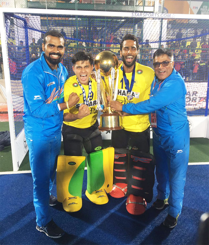 India's senior hockey team captain and goal-keeper P Sreejesh (left), India's junior hockey team 'keepers and coach pose with the Junior Hockey World Cup Trophy