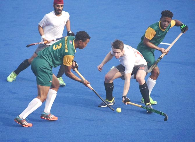 Players battle for the puck during the South Africa vs Canada Jr. World Cup Hockey match in Lucknow on Saturday