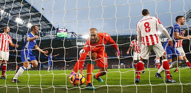 Goalkeeper Lee Grant of Stoke City grabs the ball as Gary Cahill, right, of Chelsea celebrates as he scores the opening goal during the Premier League match