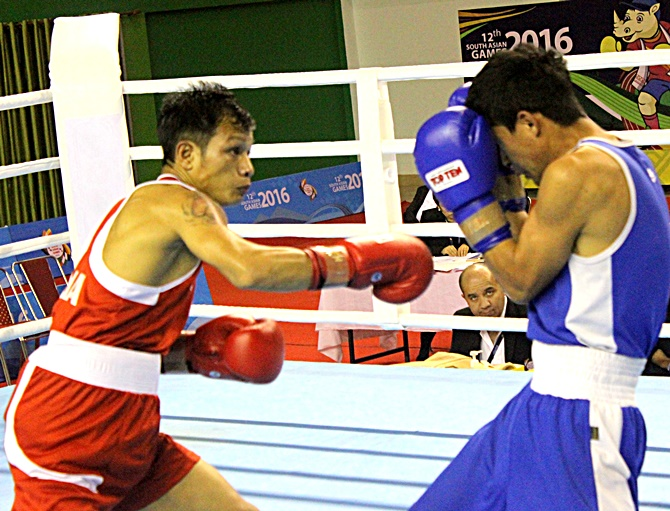 India's Devendro Singh, left, throws a jab at his opponent during the South Asian Games in Shillong
