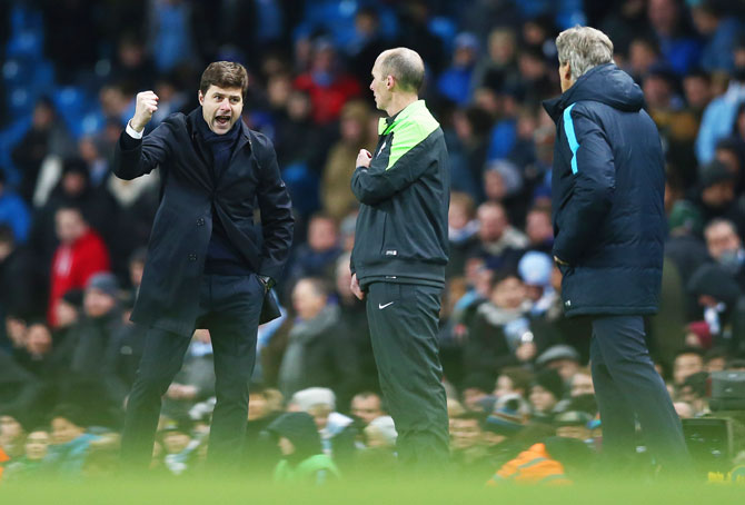 Tottenham Hotspur's manager Mauricio Pochettino (left) celebrates victory as Manchester City manager Manuel Pellegrini (right) looks on