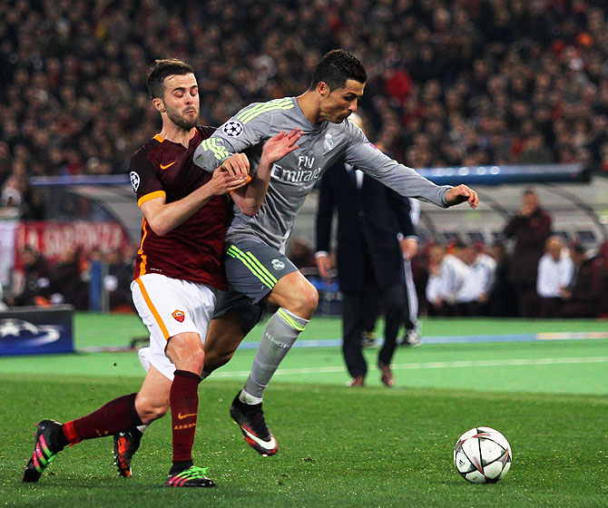 Real Madrid's Cristiano Ronaldo (right) wins the ball in a challenge against AS Roma's Miralem Pjanic