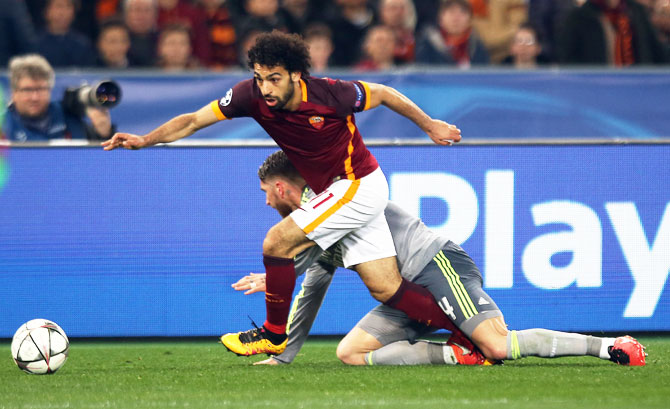 AS Roma's Mohamed Salah (left) runs with the ball past Real Madrid's Sergio Ramos