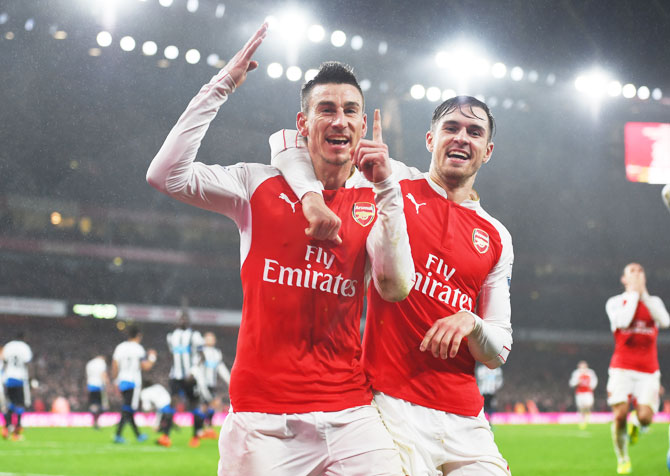 Arsenal's Laurent Koscielny (left) celebrates with his teammate Aaron Ramsey after scoring his team's first goal against Newcastle United during their Barclays English Premier League match at Emirates Stadium in London on Saturday