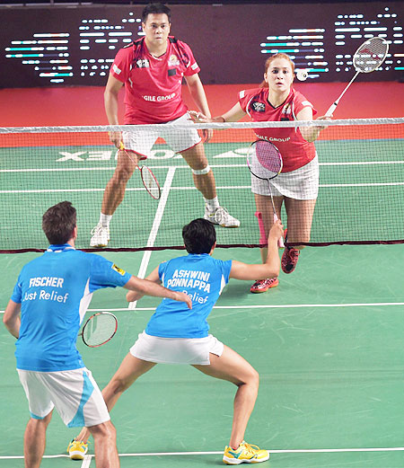 Hyderabad Hunters' Jwala Gutta, and Markis Kido (Red) pkay a return against Bangaluru Topguns' Ashwini Ponnappa and JF Nielse (Blue) in their mixed doubles match at the Premier Badminton League in Mumbai on Sunday