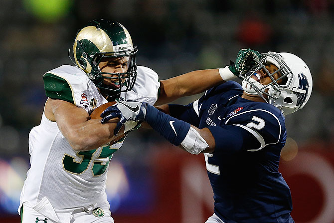 Running back Izzy Matthews #35 of the Colorado State Rams stiff arms defensive back Asauni Rufus #2 of the Nevada Wolf Pack as he rushes the football during the Nova Home Loans Arizona Bowl American Football match at Arizona Stadium in Tucson, Arizona on Tuesday, on December 29 2015