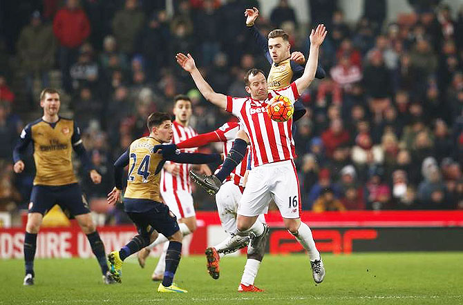 Arsenal's Calum Chambers and Stoke's Charlie Adam vie for possession during an aeriel duel