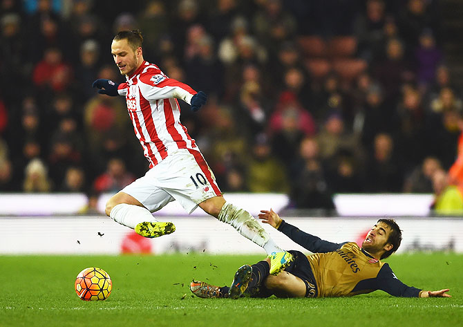 Stoke City's Marko Arnautovic is tackled by Arsenal's Mathieu Flamini during their Barclays English Premier League match at Britannia Stadium in Stoke on Trent on Sunday
