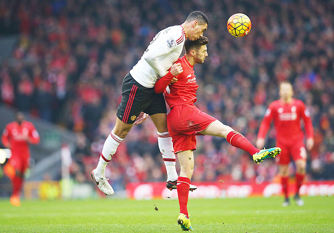 Manchester United's Chris Smalling wins a header as he duels with Liverpool's Adam Lallana