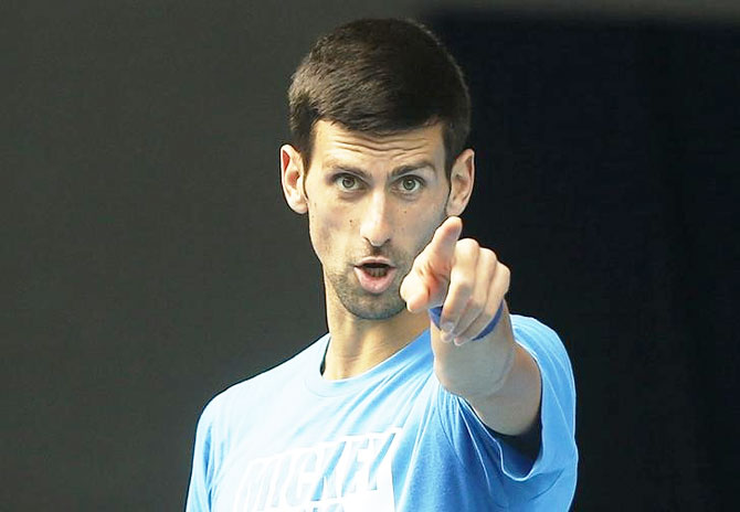 Serbia's Novak Djokovic gestures during a practice session on the eve of his final match against Britain's Andy Murray, at the Australian Open tennis tournament at Melbourne Park