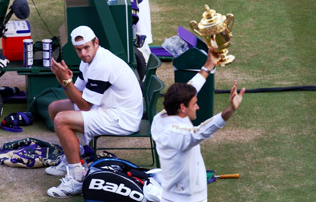 Andy Roddick looks despondent as Roger Federer celebrates