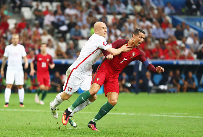 Portugal'S Cristiano Ronaldo is challenged by Poland'S Michal Pazdan in the penalty area during their Euro 2016 quarter final match between Poland and Portugal at Stade Velodrome on June 30, 2016 in Marseille, France
