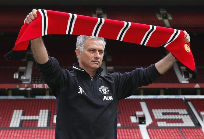 New Manchester United manager Jose Mourinho poses ahead of the press conference at Old Trafford