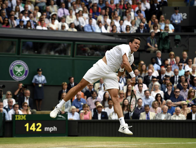 Milos Raonic serves during his match against Roger Federer