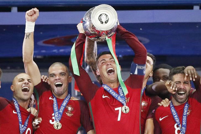 Portugal's Cristiano Ronaldo celebrates with Pepe, Ricardo Quaresma and Joao Moutinho and the trophy after winning Euro 2016 on Sunday