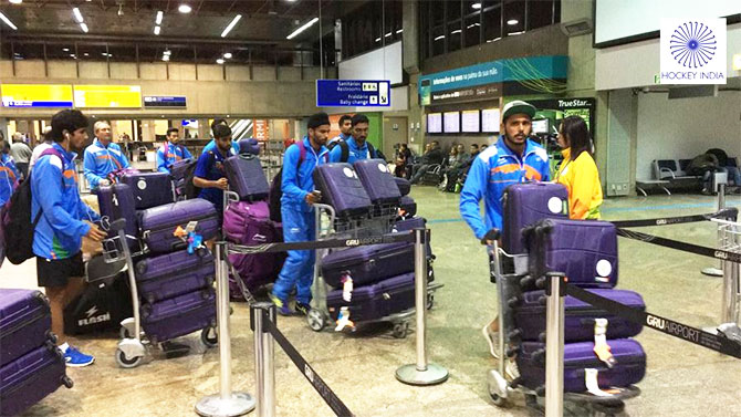 Indian hockey players make their way through the airport on arrival in Rio de Janeiro for the Olympic Games starting August 5