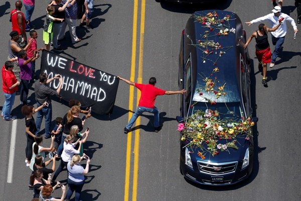"A banner stating ""We Love You Mohammad"" is displayed as well-wishers touch the hearse carrying the body of the late boxing champion Muhammad Ali on June 11"