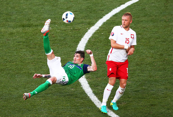 Northern Ireland's Kyle Lafferty attempts an overhead kick as a Polish player watches during their Euro 2016 Group C match at Allianz Riviera Stadium in Nice, on Sunday, June 12