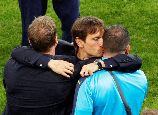 Italy head coach Antonio Conte can't hide his excitement as celebrates with team officials after his team's victory over Belgium in their Group E match in Lyon on Monday, June 13.