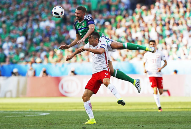 Poland's Robert Lewandowski (right) and Northern Ireland's Gareth McAuley are involved in an aerial challenge as they vie for possession during their Group C match in Nice on Sunday, June 12.