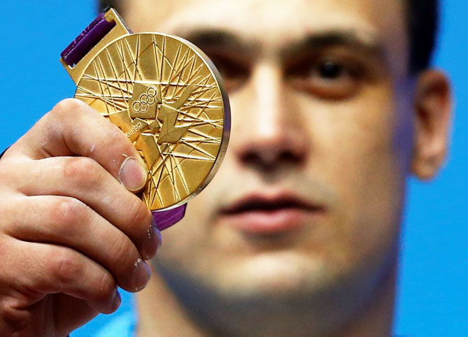 Kazakhstan's Ilya Ilyin poses with his gold medal of the men's 94Kg weightlifting competition at the ExCel venue at the London 2012 Olympic Games August 4, 2012