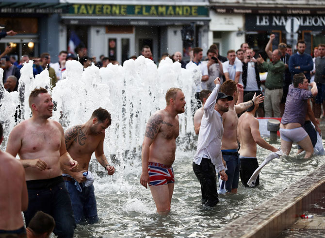 England fans chant songs and play in a fountain in Lille