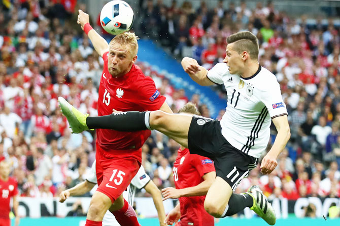 Germany's Toni Kroos (right) battles for the ball with Poland's Kamil Glik