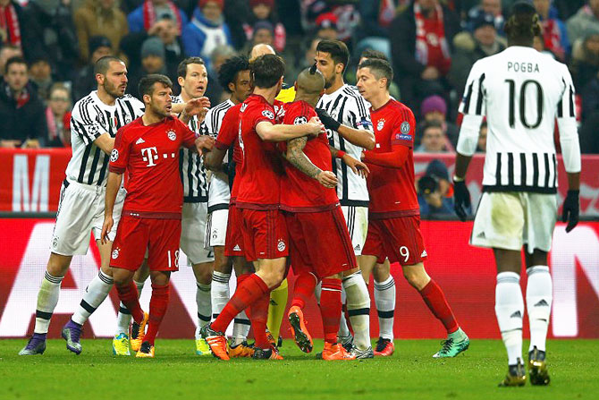 Bayern Munich's Arturo Vidal and Juventus' Juan Cuadrado are restrained by teammates as they argue