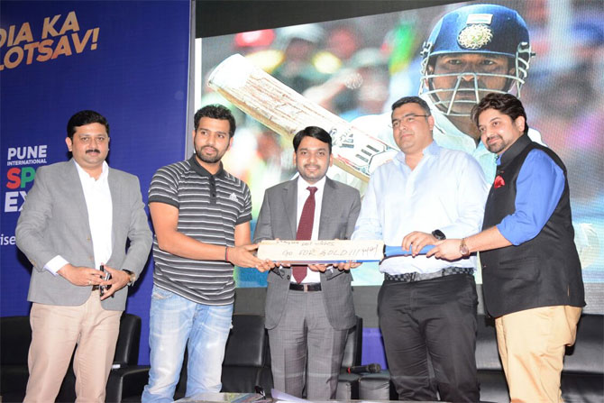 Rohit Sharma presents a signed bat to Gagan Narang at the the Pune International Sports Expo (PISE) at the College of Agriculture Grounds in Pune on Thursday