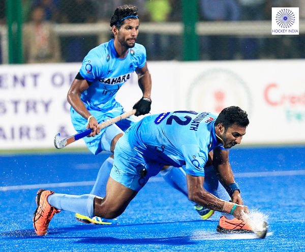 India's VR Raghunath plays a drag flick as teammate Rupinder Pal Singh watches