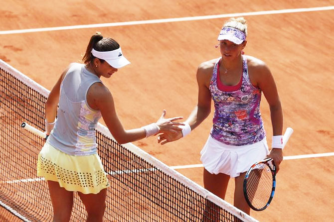 Garbine Muguruza greets Yanina Wickmayer at the net after the win
