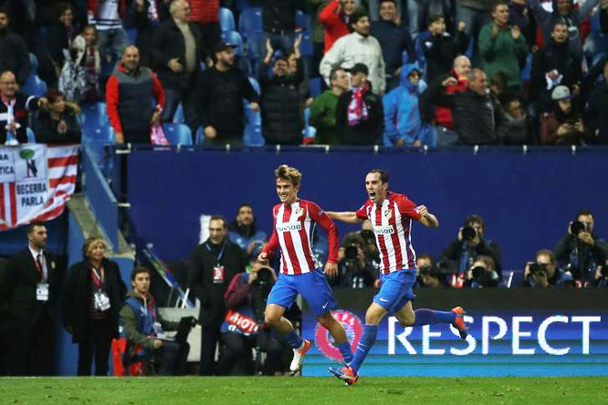 Atletico Madrid's Antoine Griezmann celebrates his goal with teammate Diego Godin during their UEFA Champions League match against Rostov at Vicente Calderon stadium, Madrid, on Tuesday