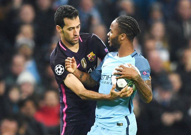 Manchester City's Raheem Sterling and Barcelona's Sergio Busquets clash