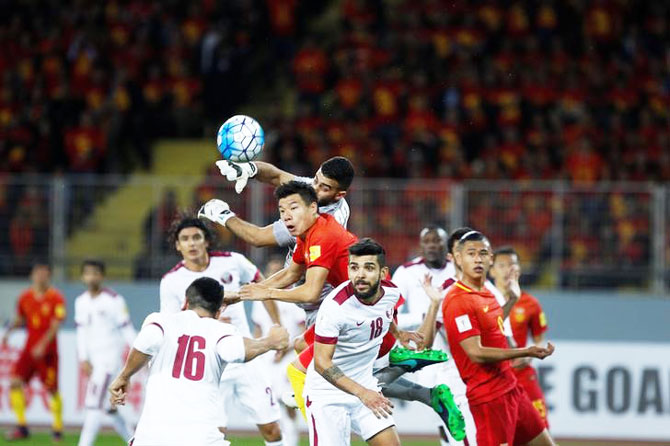 Mei Fang of China and Saad Al Sheeb, Luiz Mairton Junior of Qatar vie for possession during their World Cup 2018 QualifierIN Kunming, China, on Tuesday