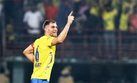 Kerala Blasters' Aaron Hughes celebrates after scoring against Pune City FC on Friday