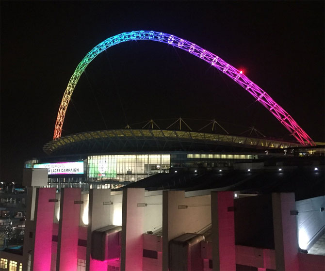 Wembley Stadium lit up in colours of the rainbow