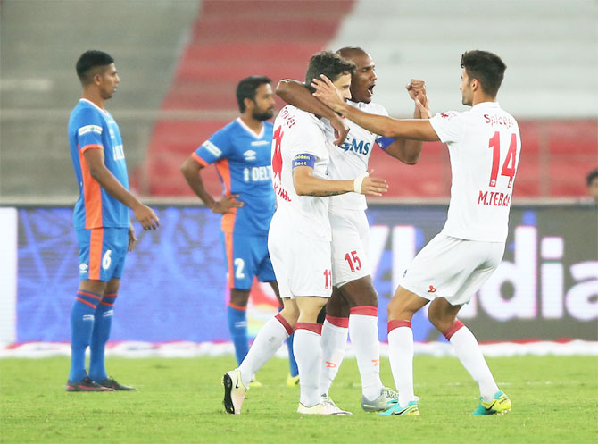 Players of Delhi Dynamos celebrate the hattrick by teammate Marcelo Pereira during their ISL match against FC Goa on Sunday