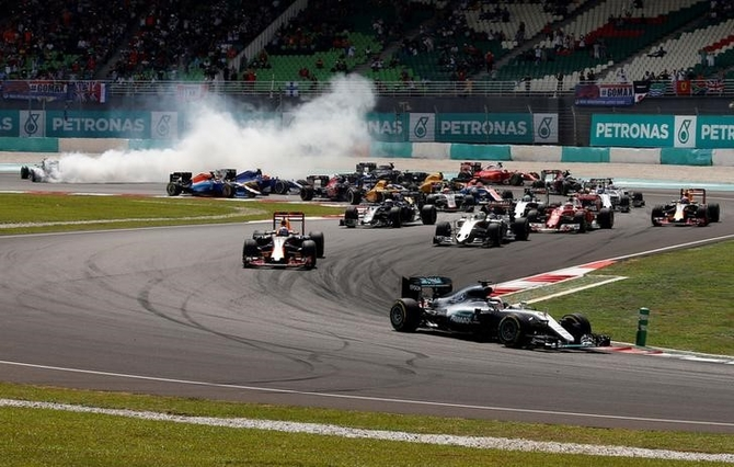 Mercedes' Lewis Hamilton of Britain leads as Mercedes' Nico Rosberg of Germany skids to the back during the first lap of the Malaysian GP