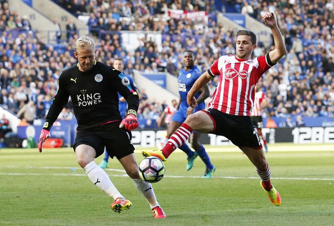 Southampton's Shane Long wins the ball as Leicester City's Kasper Schmeichel looks on