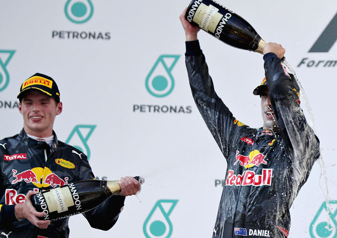 Daniel Ricciardo of Australia and Red Bull Racing and Max Verstappen of Netherlands and Red Bull Racing celebrate on the podium after the Malaysian GP