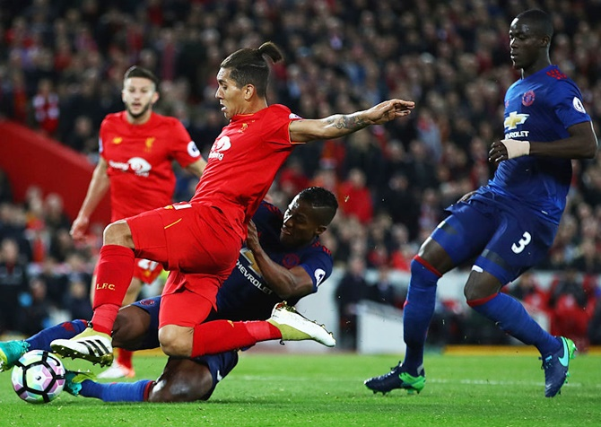 Antonio Valencia of Manchester United tackles Roberto Firmino of Liverpool