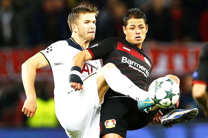 Bayer Leverkusen's Javier Hernandez and with Tottenham's Eric Dier vie for possession