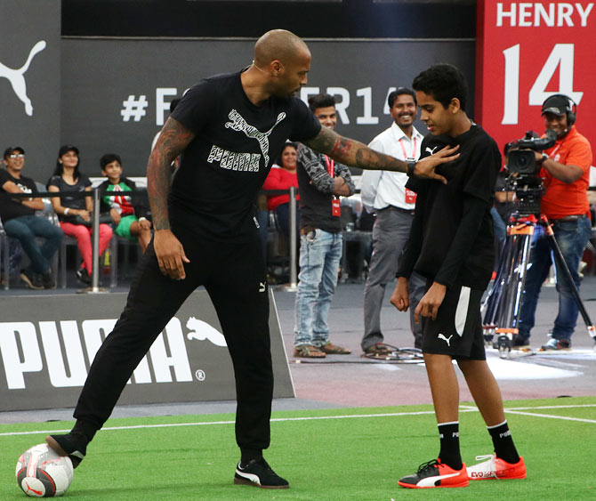 Thierry Henry 'challenges' a participant as he tries to win the ball during the training session