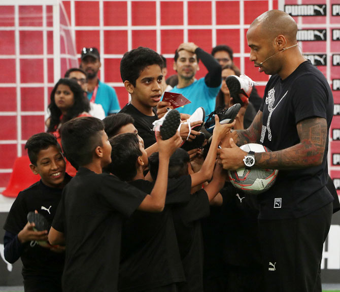 Thierry Henry obliges his young fans with autographs after the event