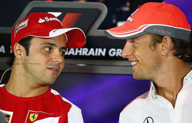 F1 drivers Felipe Massa and Jenson Button talk while attending the drivers press conference