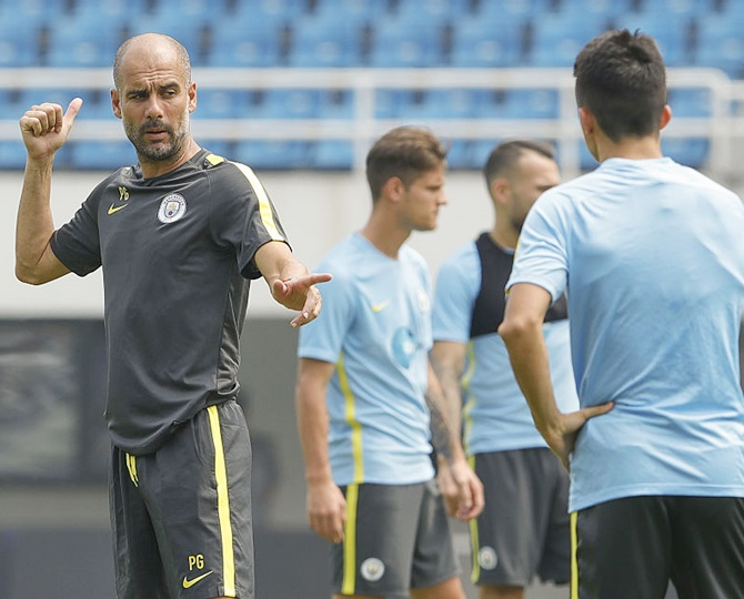 Manchester City's manager Pep Guardiola gestures during the pre-game training