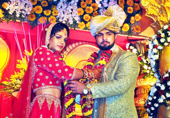Indian wrestler Sakshi Malik with and her husband and fellow wrestler Satyawart Kadian exchange garlands during their wedding ceremony in Rohtak on Sunday